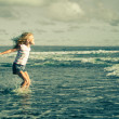 Little girl jumping on the beach at blue sea shore in summer va — Stock Photo