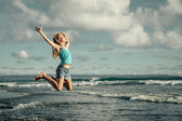 Teen girl  jumping on the beach at blue sea shore in summer vaca — Stock Photo