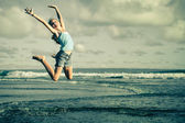 Teen girl  jumping on the beach at blue sea shore in summer vaca — Zdjęcie stockowe