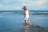 Glad liten flicka promenader på stranden under dagarna — Stockfoto