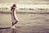Ledsen liten flicka promenader på stranden under dagarna — Stockfoto