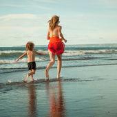 Mor och son spelar på stranden under dagarna — Stockfoto