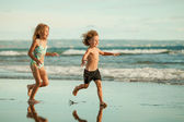 Happy kids playing on beach in the day time — Stock Photo