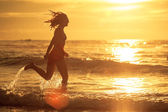 Woman running at the beach in the dawn time — Stock Photo