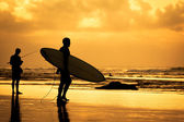 Surfer silhouette during sunset — Stock Photo