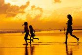счастливая семья, играя на пляже в то время рассвета — Стоковое фото