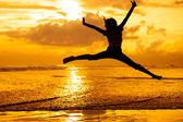 счастливая девушка прыжки на пляже на время рассвета — Стоковое фото