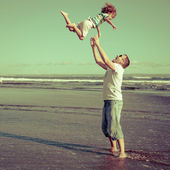 Father and son playing on the beach in the day time — Stock Photo