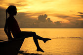 Happy teen girl sitting on beach at the dawn time — Stock Photo
