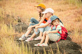 Three little kids with backpack sitting on the footpath in the m — Stock Photo