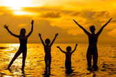 Happy family standing on the beach at the dawn time — Stock Photo