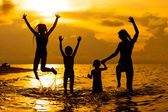 Happy family playing at the beach in the dawn timeh — Stok fotoğraf