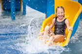Teen girl playing in the swimming pool on slide — Stock Photo