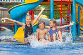 Three little kids playing in the swimming pool — Stock Photo