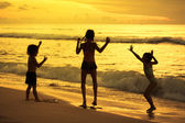 Happy children playing at the beach at the dawn time — Stock Photo