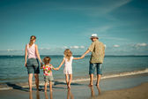 Happy family walking at the beach at the day time — Stock Photo