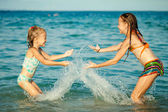 Happy little girls playing at the beach at the day time — Stok fotoğraf