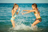 Happy little girls playing at the beach at the day time — Stockfoto