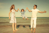 Happy family playing at the beach at the day time — Stock Photo