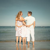 Happy family standing at the beach at the day time — Stock Photo