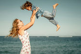 Mother and  son playing on the beach in the day time — Stock Photo
