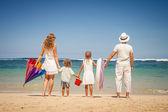 Glückliche familie stehen am strand an der tageszeit — Stockfoto