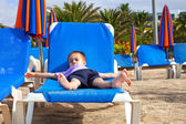 A child lying flat on a sunbed — Stock Photo