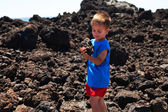 Child holding a piece of set lava — Stock Photo