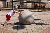 Dítě tlačí velká těžká koule — Stock fotografie