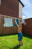 Child hanging his shirts — Stockfoto