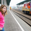 Girl on railway station platform - Stock Photo