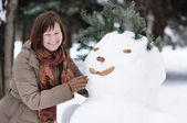 Happy middle age woman and snowman — Stockfoto