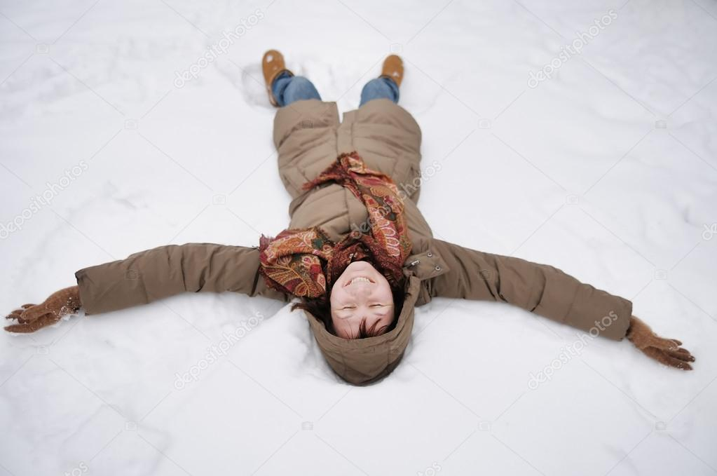 Winter fun - snow angel - happy middle age woman playing in snow  Stock Photo #14551379