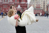 Groom holding bride in his arms — Stock Photo