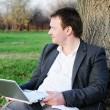 Middle age man with laptop outdoors — Stockfoto