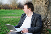 Middle age man with laptop outdoors — Stock Photo