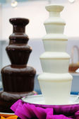 Delicious chocolate fondue fountains — Stock Photo