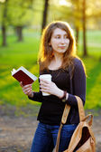 Young woman with cup of coffee and book — Stock Photo