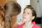 Bride applying wedding make-up by make-up artist (focus on brush) — Stock Photo