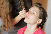 Young woman applying make-up by professional make-up artist — Stock Photo