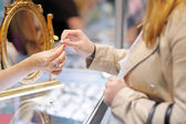 Woman trying wedding rings at a jeweler — Stock Photo