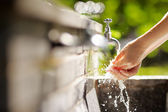 Woman washing hands in a city fountain  — Foto de Stock