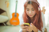Young asian woman listening to music — Stock Photo