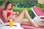 Woman relaxing on sunbed with smart phone — ストック写真