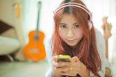 Joven asiática escuchando música — Foto de Stock