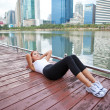 Woman exercising sit ups outside — Stock Photo