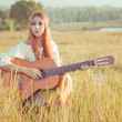 Hippie girl playing guitar on grass — Stock Photo #38982945