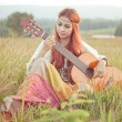 Hippie girl playing guitar on grass — Stock Photo