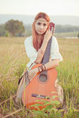Hippie girl playing guitar on grass — Foto Stock