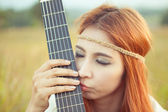Hippie girl with guitar on grass — Stock Photo